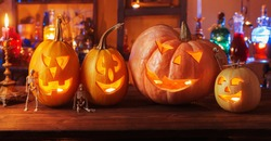 Halloween pumpkins with candles and magic potions at night indoor