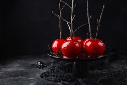 Halloween red caramelized candy apples, black background
