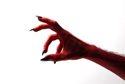 Halloween red devil monster hand with black fingernails against a plain background