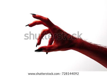 Halloween red devil monster hand with black fingernails against a plain background