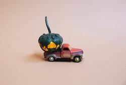 Halloween red vintage truck with orange green pumpkin. Minimal style for autumn season.