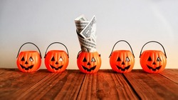 Halloween savings concept, pumpkin buckets and one with dollar money on old wood table in bright orange light