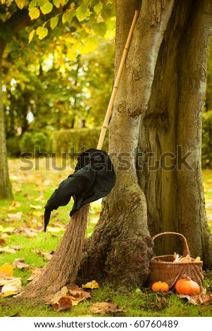 Halloween scene of a witch hat, broom and pumpkin basket against a hollow autumn tree