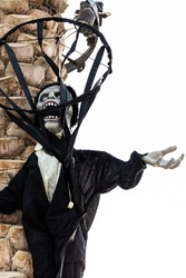Halloween screaming zombie monster puppet decoration hanging on a palm tree trunk in Dubai, United Arab Emirates.
