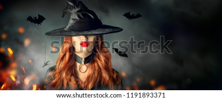 Halloween Sexy Witch portrait. Beautiful young woman in witches hat with long curly red hair and bright lips. Over spooky dark magic forest background. Wide Halloween party art design