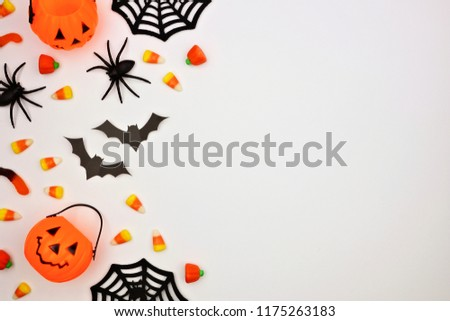 Halloween side border of scattered candy and decor. Flat lay over a white background. Copy space. #1175263183