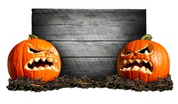 Halloween sign with two scary pumpkins in front of an old blank weathered wood banner as a concept for a creepy advertisement and marketing announcement for a harvest time party.