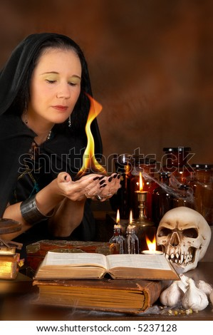 Halloween sorceress holding a fire flame in her hands