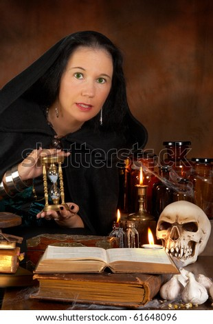 Halloween sorceress showing a hourglass and witchcraft books - stock photo
