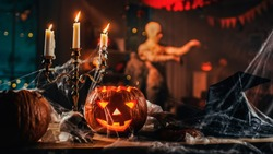 Halloween Still Life Colorful Theme: Scary Decorated Dark Room with Table Covered in Spider Webs, Burning Pumpkin, Candlestick, Witch's HatбSkeleton. In the Background Silhouette of Monster Walking By