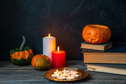 Halloween still life. Pumpkin stands on a stack of old books. A pumpkin stands on a stack of old books, candles burning nearby. Dark background.