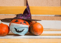 Halloween street decorations in the new reality of the COVID-19 pandemic. Three pumpkins, one of which has a witch's hat and a medical mask with a painted scary smile. On a wooden bench