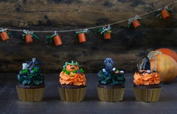 Halloween symbols, preparation for the holiday. Orange pumpkin cupcakes and wood decor. Black background