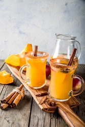 Halloween, Thanksgiving. Traditional autumn, winter drinks and cocktails. Spicy hot pumpkin sangria, with apple, cinnamon, anise. On old rustic wooden table, in glass mugs. Selective focus copy space