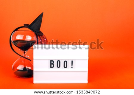 Halloween themed cinema light box on the bright orange background with funny witch hat and black sand hourglass #1535849072
