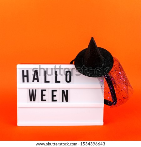 Halloween themed cinema light box on the bright orange background with funny witch hat. Square format #1534396643