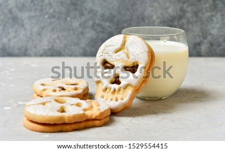 Halloween themed kids breakfast. Skull shaped cookies with a glass of milk. grey background. selective focus
