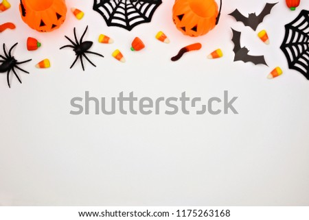 Halloween top border of scattered candy and decor. Flat lay over a white background. Copy space. #1175263168