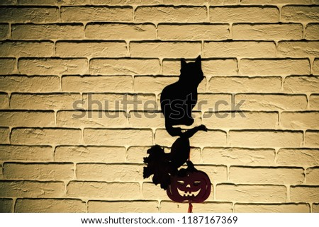 Halloween totem symbols. Holiday celebration concept. Black cat and orange pumpkin with tree leaves silhouettes paper cutouts on beige brick wall. Mystery and superstition, copy space #1187167369
