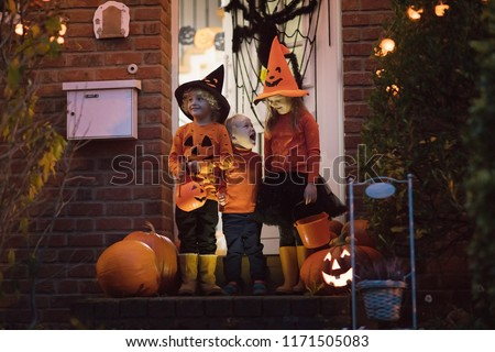 Halloween trick or treat. Children in black and orange witch costume and hat standing at house door with pumpkin and spider decoration. Kids trick or treating. Boy and girl with candy buckets.