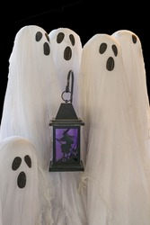 Halloween trick or treating white sheet ghosts and a black lantern with a witch and a cat inside.
