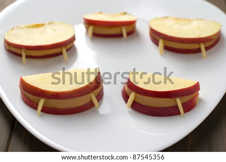 Halloween vampire apple lips in a plate on a wooden table
