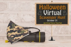 Halloween Virtual Scavenger Hunt October 31 sign next to homemade face mask and  black flashlight