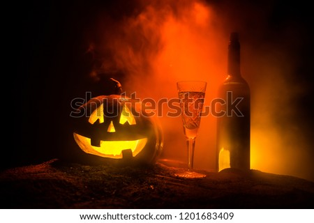 Halloween wine party theme. Glass of wine and bottle with Halloween - old jack-o-lantern on dark toned foggy background. Scary Halloween pumpkin