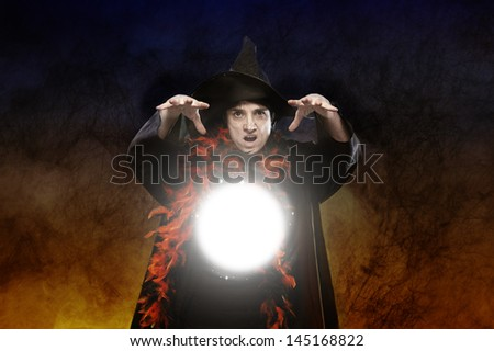 halloween witch casting a spell on dark background