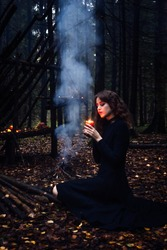 Halloween witch girl with witchcraft, near the fire, spells, in the forest. Beautiful young woman in conjuration. Spooky dark magic forest background. Wizard. Halloween party design