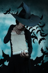 Halloween witch holding a scroll, space for text
