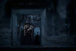 Halloween witch holding a skull standing in old damaged window with wall over cross, church, birds, dead tree and spooky cloudy sky, Halloween mystery concept