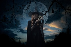 Halloween witch holding a skull standing over cross, church, crow, bat, birds, dead tree, full moon and sunset sky, Halloween mystery concept