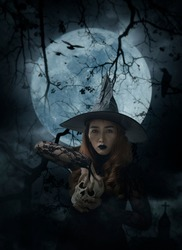 Halloween witch holding a skull standing over cross, church, crow, birds, dead tree, full moon and cloudy spooky sky, Halloween mystery concept