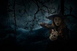 Halloween witch holding a skull standing over dead tree, crow, birds, full moon and spooky cloudy sky, Halloween mystery concept