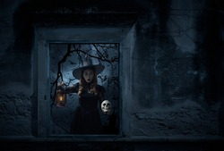 Halloween witch holding ancient lamp and skull standing in old damaged window with wall over cross, church, birds, dead tree and spooky cloudy sky, Halloween mystery concept