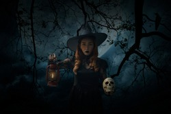 Halloween witch holding ancient lamp and skull standing over dead tree, crow, birds, full moon and spooky cloudy sky, Halloween mystery concept