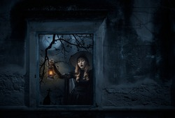 Halloween witch holding ancient lamp standing in old damaged window with wall over cross, church, birds, dead tree and spooky cloudy sky, Halloween mystery concept