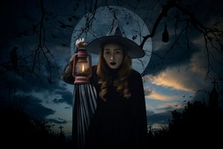 Halloween witch holding ancient lamp standing over cross, church, crow, bat, birds, dead tree, full moon and sunset sky, Halloween mystery concept