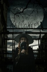 Halloween witch holding black face mask standing over damaged old wooden bridge, bird, dead tree, full moon with spooky cloudy sky, Halloween mystery concept