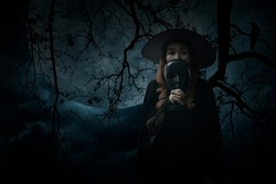 Halloween witch holding black face mask standing over dead tree, crow, birds, full moon and spooky cloudy sky, Halloween mystery concept