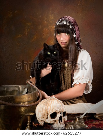 Halloween witch holding her black cat with green eyes (the book is 300 years old, no copyright problems)