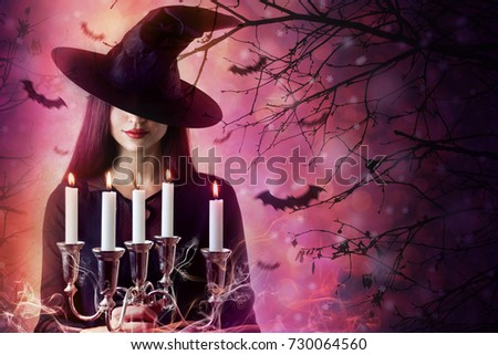 Halloween Witch in a dark forest. Beautiful young woman in witches hat. Halloween art design #730064560