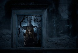 Halloween witch showing silence sign with finger over lips standing in old damaged window with wall over cross, church, birds, dead tree and spooky cloudy sky, Halloween mystery concept