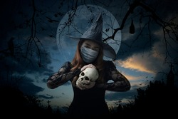 Halloween witch wearing medical face mask holding a skull standing over cross, church, crow, bat, birds, dead tree, full moon and sunset sky, Halloween and coronavirus or covid-19 concept