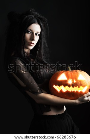Halloween witch with a broom and carved pumpkin over black background.
