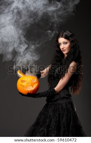 Halloween witch with a broom and smoke coming out of carved pumpkin