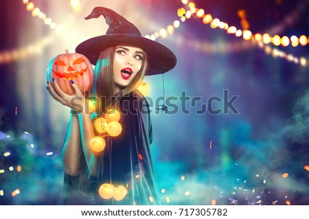 Halloween Witch with a carved Pumpkin and magic lights in a dark forest. Beautiful young surprised woman in witches hat and costume holding pumpkin. Halloween party art design #717305782
