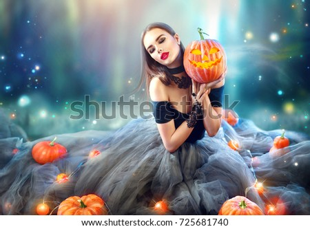 Halloween Witch with a carved Pumpkin and magic lights in a dark forest. Beautiful young surprised woman in witches hat and costume holding pumpkin. Halloween party art design. #725681740