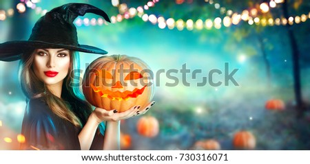 Stock Photo Halloween Witch with a carved Pumpkin and magic lights in a dark forest. Beautiful young surprised woman in witches hat and costume holding pumpkin. Wide Halloween party art design